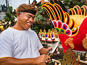 16 JULY 2016 - UBUD, BALI, INDONESIA:  A man carves a piece of bamboo for a sarcophagus for the mass cremation in Ubud. Local people in Ubud exhumed the remains of family members and burned their remains in a mass cremation ceremony Wednesday. Almost 100 people were cremated and laid to rest in the largest mass cremation in Bali in years this week. Most of the people on Bali are Hindus. Traditional cremations in Bali are very expensive, so communities usually hold one mass cremation approximately every five years. The cremation in Ubud concluded Saturday, with a large community ceremony.    PHOTO BY JACK KURTZ