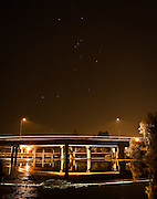 The constellation Orion the Hunter twinkles brightly enough to be seen through the glow of artificial lighting on the bridge.  A diving beaver creates a splash ring.  The loss of natural darkness around the world is now known as light pollution, which has prompted adaptions in humans and other animals.