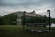 Narva, Estonia - July 23, 2015: A bench on the Estonian side of the Narva River commands a view to the Russian side, including the castle built by Ivan III of Muscovy in 1492. The Estonian side is the city of Narva; the Russian side is Ivangorod.