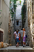 Group of tourists, two children (9 years old, 5 years old) at rear, walking through paved, stepped lane of Korcula old town. Korcula old town, island of Korcula, Croatia