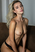 Beautiful blond haired nude woman sitting on a brown sofa looking at the camera with a provocative expression