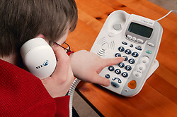 Teenage Downs Syndrome boy dialling a number on a large button telephone,