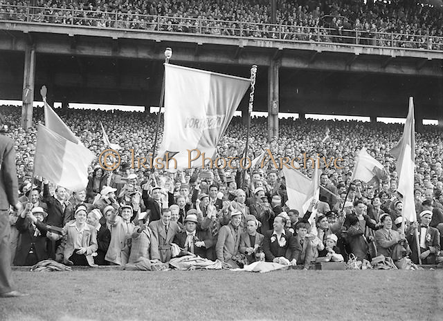 Crowds of supporters in the stands holding flags during the All Ireland Senior Gaelic Football Final Armagh v Kerry in Croke Park on the 27th September 1953. Kerry 0-13, Armagh 1-06.