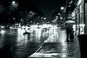 A couple stands under an umbrella on a rainy Paris street at night