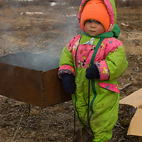 North of the Arctic Circle in Russia, a Russian toddler helps her family tend their coal-fired barbeque during a picnic near Snopa village.