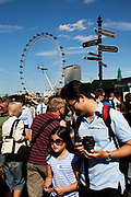 Japanese Tourists cross Westminster bridge by the River Thames at Westminter, London. With the iconic London Eye behind this is one of the busiest areas for tourism in the city.