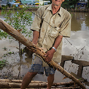 CAPTION: Nguyen Can Chau explains how the erosion barrier is constructed. He also expresses his fear of the water level rising during the night and washing away the construction materials before the barrier is finished. LOCATION: An Binh Ward, Can Tho, Vietnam. INDIVIDUAL(S) PHOTOGRAPHED: Nguen Can Chau.