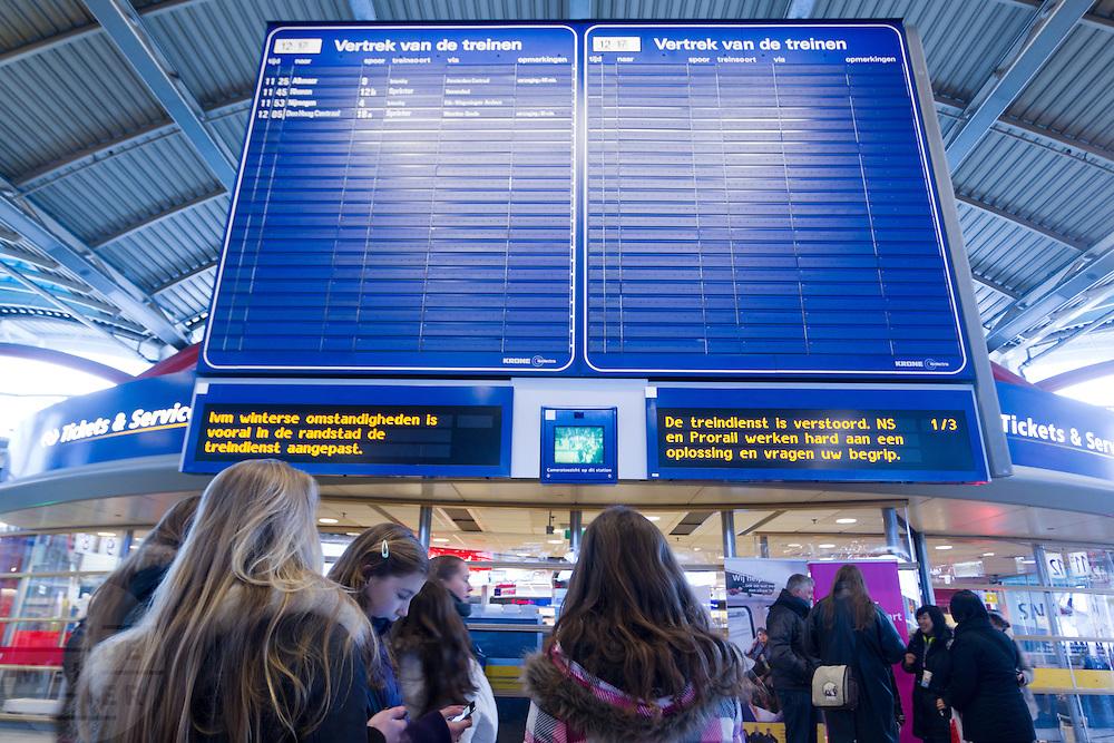 Reizigers wachten in de stationshal van Utrecht CS op de treinen. Op de aanwijsborden vragen ProRail en NS om begrip vanwege de uitval van treinen. Ondanks alle voorzorgsmaatregelen met een speciale dienstregeling, lukt het de NS en ProRail niet om de treinen vanuit Utrecht goed te laten rijden.<br /> <br /> Passengers are waiting for information when a train will leave at Utrecht CS.  In spite of al the precautions the Dutch railways are having a lot of problems with the snowfall this winter.