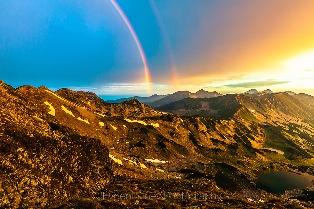 Double rainbow rises from the mountain