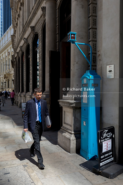 A businessman walks past one of the few remaining police signal boxes on Threadneedle Street  in the City of London, the capital's historic financial district, on 2nd August 2018, in London, England. The Police box is a public telephone kiosk or callbox for the use of members of the police, or for members of the public to contact the police. It was introduced in the United States in 1877 and was used in the United Kingdom throughout the 20th century from the early 1920s.