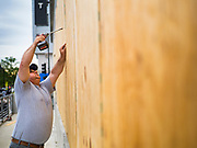 31 MAY 2020 - DES MOINES, IOWA: WILLIAM BENNETT, a worker for Hy-Vee Construction, puts plywood over shattered windows at the Hy-Vee grocery store in downtown Des Moines. The windows were shattered by rioters early Sunday morning. A group of rioters, protesting the death of George Floyd in police custody in Minneapolis, smashed windows in businesses and restaurants around the Polk County Courthouse in Des Moines. Des Moines police said they made 25 arrests Saturday night and very early Sunday morning. No one was hurt in the disturbances.     PHOTO BY JACK KURTZ