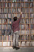 A man searching for vinyl on shelves stacked high with records at Vinyl Pimp record shop in Hackney Wick on the 29th March 2018 in East London in the United Kingdom.
