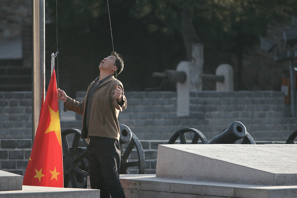 At 6am a worker at the Badaling section of The Great Wall raises the Chinese national flag.