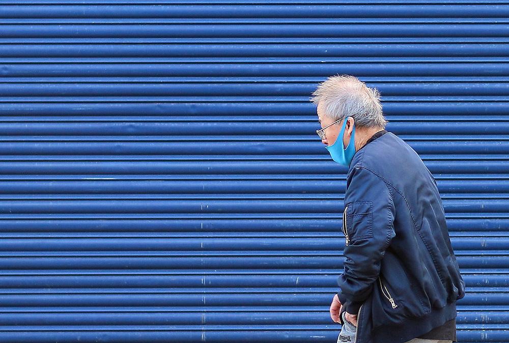 6th March, 2021. Cheltenham, England. A man wearing a mask walks through the town centre.