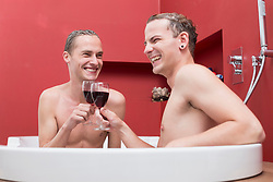 Homosexual couple having glass of red wine in bathtub, smiling