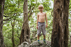 Portrait of boy standing on rock at forest, Mauritius