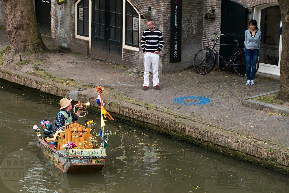 Muzikant Reinier Sijpkens vaart met zijn muziekboot Notendop door de Oudegracht in Utrecht.<br /> <br /> Musician Reinier Sijpkens sails with his so called music boat Notendop in the canals of Utrecht.