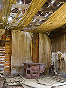 Interior of 1890s house with old rusting stove, American frontier architecture preserved at Elkhorn State Park, Montana, USA. The silver, gold and lead mines at Elkhorn began booming in 1875, then declined in 1892 as silver prices dropped. A few miners still work the Elkhorn mines and live in private homes nearby, within Beaverhead-Deerlodge National Forest.  Directions: I-15 at Boulder exit, 7 miles south on Montana 69, then 11 miles north on county graveled road.  (Lat 46.275,  Lng  -111.946)