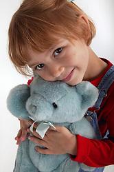 Portrait of young girl cuddling teddy bear,
