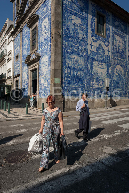 A quirky scene of a patterned wearing lady looked at strangely by a gentlemen, both crossing the Rua de Fernandes Tomas with Azulejo tiles on the exterior of Capela Das Almas, on 19th July, in Porto, Portugal. The Churchs magnificent panels depict scenes from the lives of various saints, including the death of St Francis and the martyrdom of St Catherine. Eduardo Leite painted the tiles in a classic 18th-century style, though they actually date back only to the early 20th century.