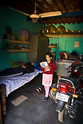 Jasbir Kaur prepares to leave for school whilst her father sleeps in family bedroom, Chita Kalaan village, Punjab, India