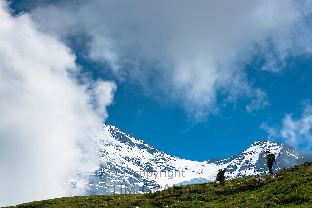 Tourist taking photograph on walking trail by the Jungfrau mountain in the Swiss Alps, Bernese Oberland, Switzerland