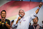 """09 MAY 2014 - BANGKOK, THAILAND: SUTHEP THAUGSUBAN (right) speaks from the main PDRC stage in Lumpini Park Friday. He went onto lead a march with thousands of anti-government protestors to Government House in the Dusit neighborhood of Bangkok. Thousands of Thai anti-government protestors took to the streets of Bangkok Friday to start their """"final push"""" to bring the popularly elected of government of Yingluck Shinawatra. Yingluck has already been forced out by a recent court ruling that forced her to resign and she is facing indictment by the National Anti Corruption Commission of Thailand for alleged improprieties related to a government rice price support scheme. The protestors Friday were marching to demand that she not be allowed to return to politics. The courts have not banned her party, Pheu Thai, which has formed an interim caretaker government to govern until elections expected in July, 2014. Suthep Thaugsuban, secretary-general of the People's Democratic Reform Committee (PDRC),  said the president of the Supreme Court and the new senate speaker, who would be selected Friday, should set up an """"interim people's government and legislative assembly."""" He went onto say that if they didn't, he would.     PHOTO BY JACK KURTZ"""