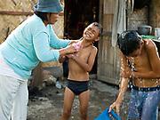 Jilena Pineda (50) washes her sons before school, Barangay Numo, Esperanza, Sultan Kudarat province, Mindanao Island, The Philippines.