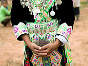 White Hmong girl holding a cloth ball for playing the ball throwing game of 'pov pob' at Ban Hauywai Hmong New Year festival, Phongsaly province, Lao PDR. 'Pov pob' is a formalised courting ritual where unmarried men and women face each other in a line and toss cloth balls to one another using only one hand. The Hmong celebration of New Year is based on the lunar calendar. This important time is an opportunity to honour ancestors and spirits through offerings and rituals and to partake in games, sports, feasts, shows, bullfights and courtship. The Hmong are the third largest ethnic group in Laos. One of the most ethnically diverse countries in Southeast Asia, Laos has 49 officially recognised ethnic groups although there are many more self-identified and sub groups. These groups are distinguished by their own customs, beliefs and rituals.