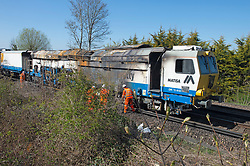 © Licensed to London News Pictures 23/04/2021. Dunton Green, UK. A fire damaged freight train with engineers on scene. A freight train has caught fire this morning on the tracks outside Dunton Green Train Station in Kent, firefighters extinguished the blaze and engineers are now working to remove it. Photo credit:Grant Falvey/LNP