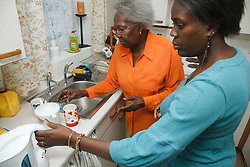 Mother and daughter doing washing up.