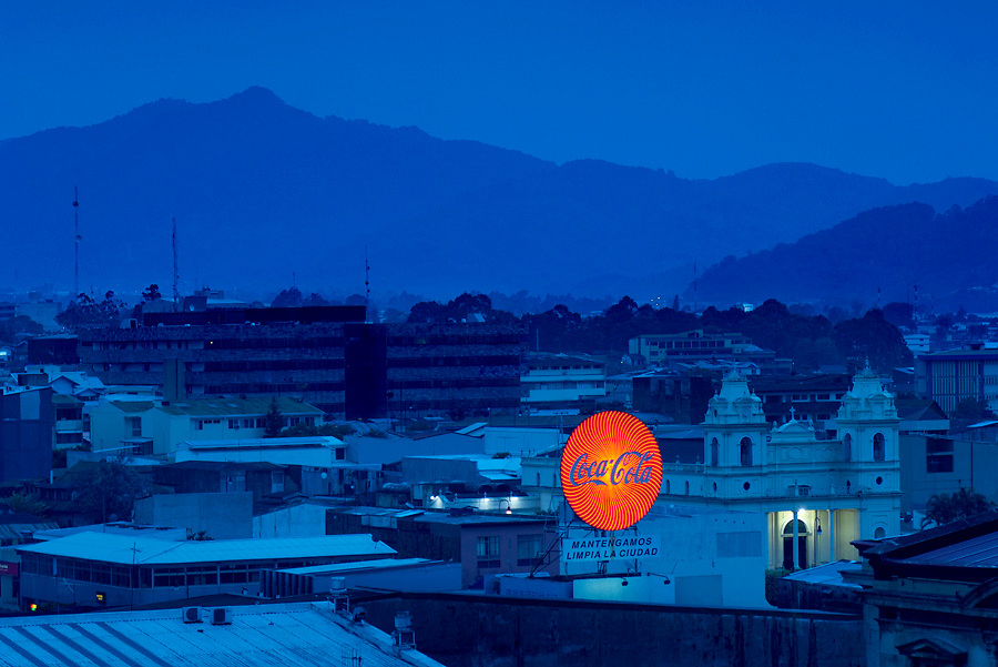 The Central Volcanic Cordillera backdrops the red neon Coca-Cola sign, which is a marker for the main bus station, and the Church of La Soledad.