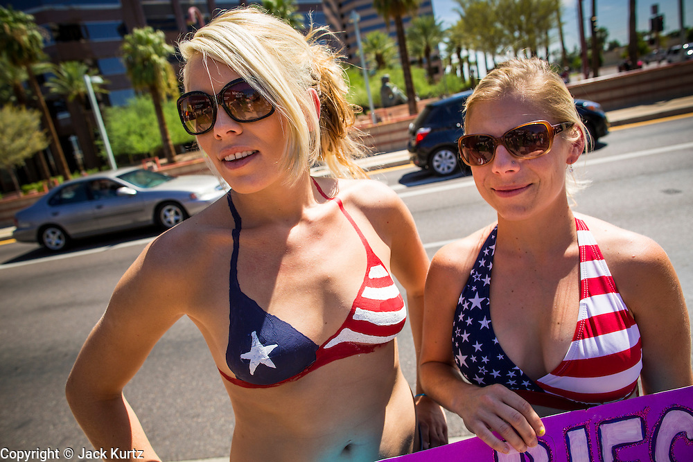 26 MARCH 2012 - PHOENIX, AZ: ELIZABETH CONLEY, left, from Phoenix, and YVONNE HARAMBASIC, from El Mirage, watch a topless protest in Phoenix. Conley had a bikini top painted on and Harambasic wore a real bikini top. About 40 people marched through central Phoenix Sunday to call for a constitutional amendment to give women the same right to go shirtless in public that men have. The Phoenix demonstration was a part of a national Topless Day of Protest. Phoenix prohibits women from going topless in public so protesters, women and men, covered their nipples and areolas with tape. The men did it to show solidarity with the women marchers.    PHOTO BY JACK KURTZ