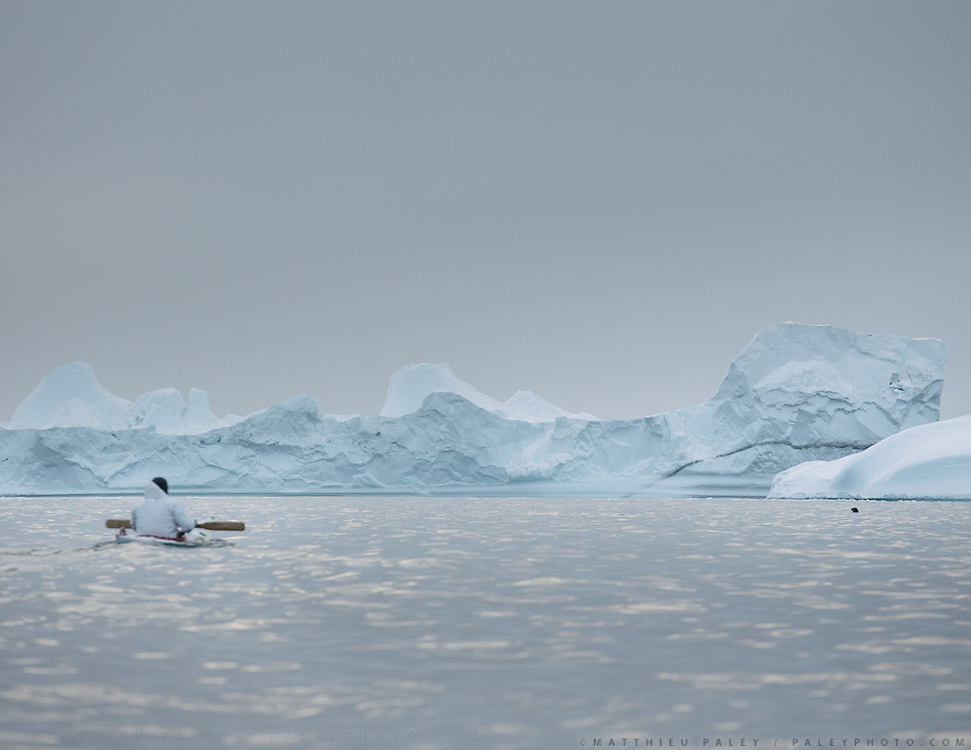 Head of a seal is visible as a black dot on the right of image. Going seal hunting on a kayak with hunter Magnus Eraksen. Life in and around the small Inuit settlement of Isortoq (population of 64), in East Greenland.