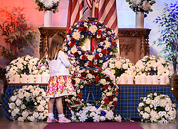 A young girl from the congregation looks at the wreaths after a special memorial service to mark the 15th anniversary of 9/11 at Cathcart Old Parish Church, Glasgow.