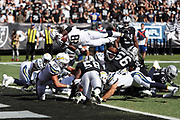 Los Angeles Chargers running back Melvin Gordon (28) dives over a pile of players into the end zone for a one yard touchdown that ties the second quarter score at 7-7 during the 2017 NFL week 6 regular season football game against the against the Oakland Raiders, Sunday, Oct. 15, 2017 in Oakland, Calif. The Chargers won the game 17-16. (©Paul Anthony Spinelli)