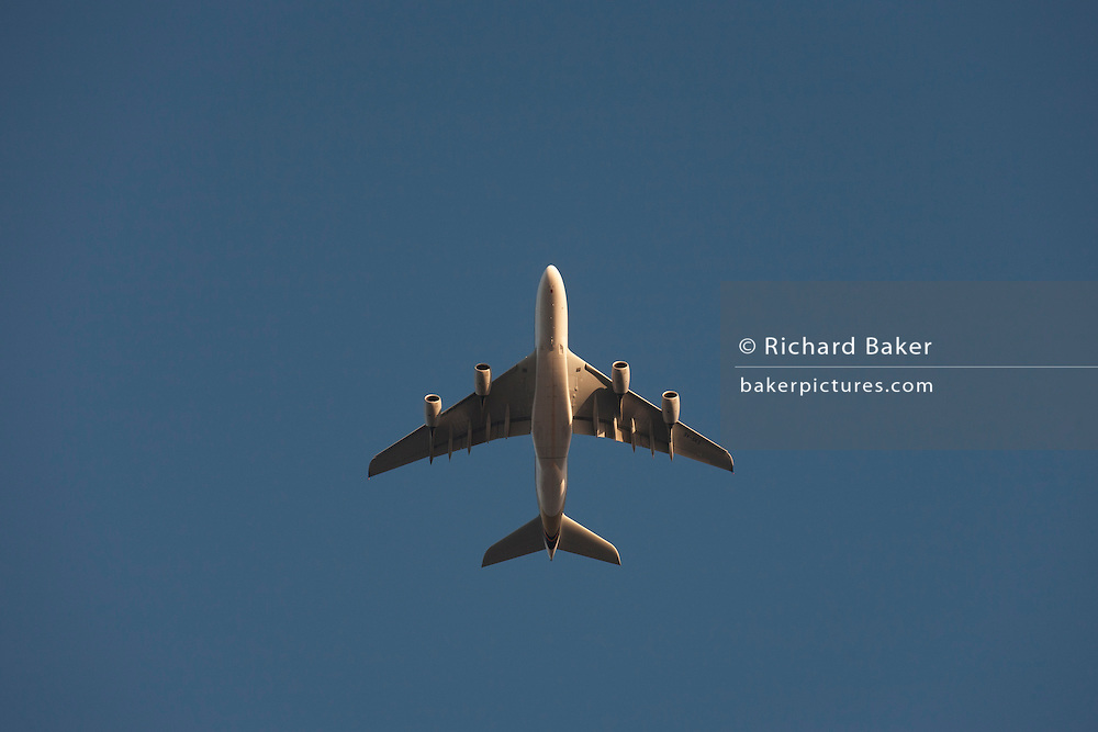 Airbus A380 9V-SKS flies overhead in south London low sunlight.