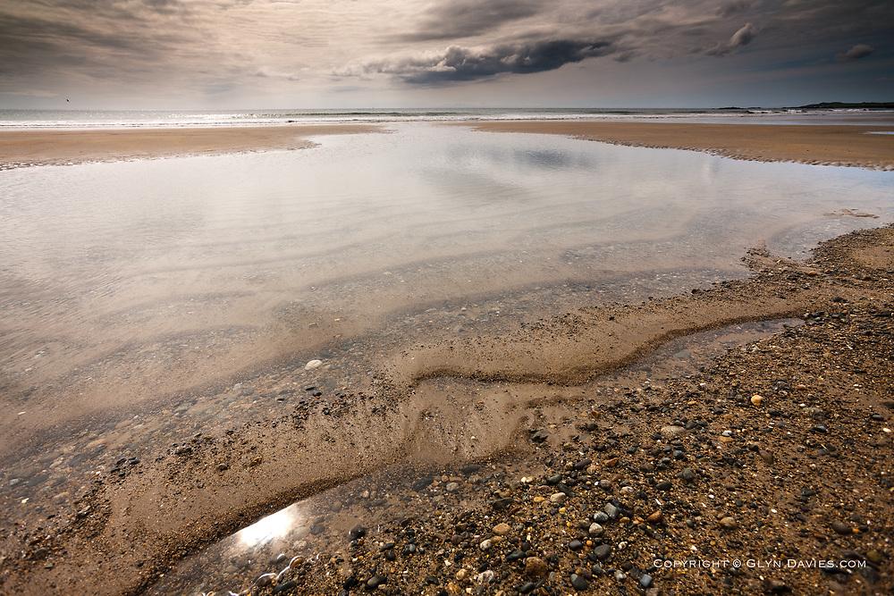 Pools and ripples left by retreating ebb tide at Traeth Tyn Tywyn Beach, Rhosneigr, Anglesey