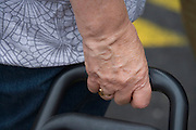 close up of hands holding a suitcase on wheels