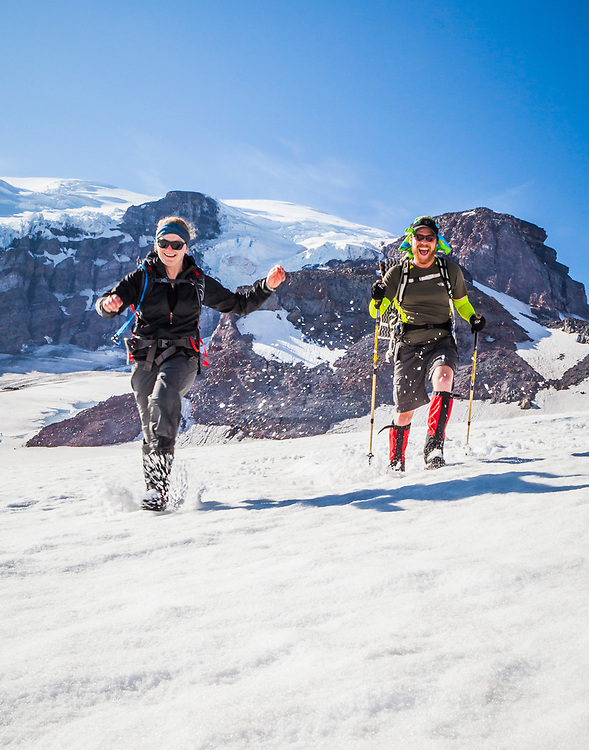A young man and woman running down the Muir snow field on Mount Rainier, Washington, USA.