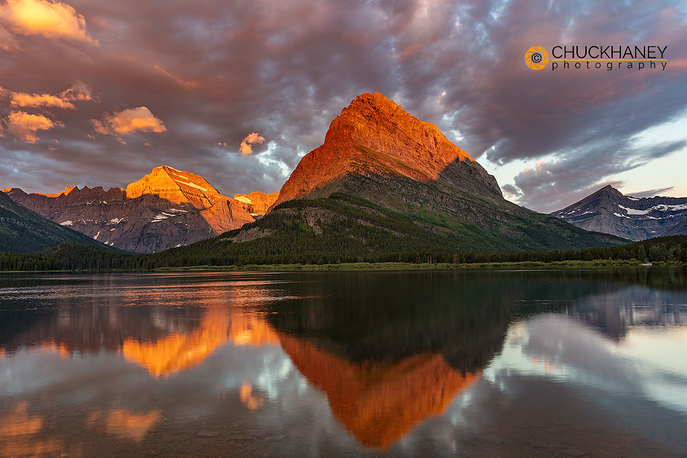 Sunrise clouds light up over Swiftcurrent Lake in Glacier National Park, Montana, USA