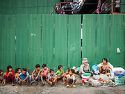 31 AUGUST 2013 - BANGKOK, THAILAND:       Children who live in construction worker housing on Sukhumvit Soi 22 sit on the curb in front of the complex. The workers are building the Bhiraj Tower, a new office/retail complex under construction on Soi 35 Sukhumvit Road. It will be approximately 45 storeys when completed. The workers live in a complex of corrugated metal dorms about 1 kilometer from the construction site. They walk to and from the site every day.  PHOTO BY JACK KURTZ