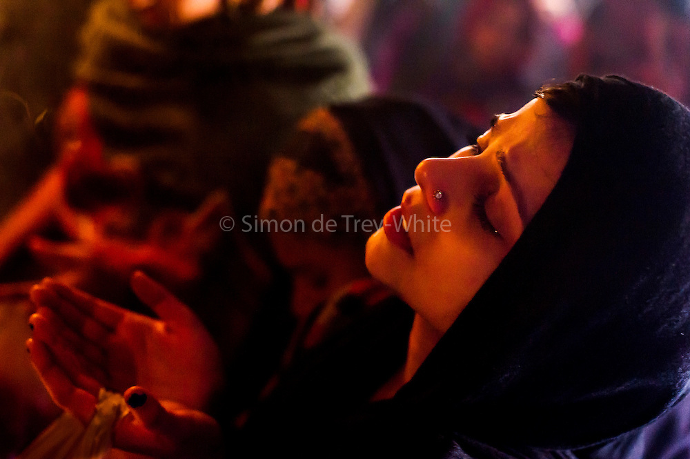 4th December 2014, New Delhi, India. A Muslim woman prays for her wishes to be granted by Djinns in the ruins of Feroz Shah Kotla in New Delhi, India on the 4th December 2014<br /> <br /> PHOTOGRAPH BY AND COPYRIGHT OF SIMON DE TREY-WHITE a photographer in delhi<br /> + 91 98103 99809. Email: simon@simondetreywhite.com<br /> <br /> People have been coming to Firoz Shah Kotla to leave written notes and offerings for Djinns in the hopes of getting wishes granted since the late 1970's. <br /> Feroz Shah Tughlaq (r. 1351–88), the Sultan of Delhi, established the fortified city of Ferozabad in 1354, as the new capital of the Delhi Sultanate, and included in it the site of the present Feroz Shah Kotla. Kotla literally means fortress or citadel. The pillar, also called obelisk or Lat is an Ashoka Column, attributed to Mauryan ruler Ashoka. The 13.1 metres high column, made of polished sandstone and dating from the 3rd Century BC, was brought from Ambala in 14th century AD under orders of Feroz Shah. It was installed on a three-tiered arcaded pavilion near the congregational mosque, inside the Sultanate's fort. In centuries that followed, much of the structure and buildings near it were destroyed as subsequent rulers dismantled them and reused the spolia as building materials.