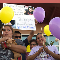 Community members hold balloons, flowers, and signs outside the Zuni Wellness Center Thursday as part of the Suicide Prevention Day to promote awareness of the issue. After walking through the village of Zuni, participants released the balloons in front of the wellness center.