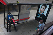 With a further 89 UK covid victims in the last 24hrs, bringing the total victims to 43,995 during the Coronavirus pandemic, a man wearing social distance t-shirt (worn by railway station concourse employees), sits at a bus stop next to an ad for supporting NHS (National Health Service) key workers, on 2nd July 2020, in London, England.