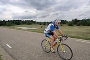 Een eenzame racefietser op de dijk in de Ooijpolder bij Nijmegen.<br /> <br /> A lonely cyclist on a dike in the Ooijpolder near Nijmegen.