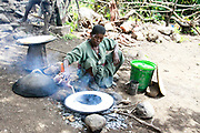 Africa, Ethiopia, Lalibela, Woman cooks Injera (Injera is a sourdough-risen flatbread with a unique, slightly spongy texture. Traditionally made out of teff flour, it is a national dish in Ethiopia and Eritrea). on a mogogo over a fire