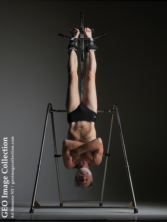 Man hanging from an inversion table designed to relieve back pain.