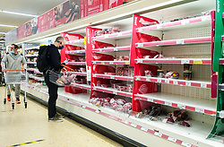© Licensed to London News Pictures. 23/12/2020. London, UK. A shopper looks at nearly empty shelves of meat products in Sainsbury's supermarket in north London, just two days before Christmas day. A number of supermarkets have warned that some items may run low this week. France has ended its ban on the UK arrivals and has reopened its borders with the UK under the condition of a negative COVID-19 test. It is expected that the backlog of lorries wishing to travel to Europe will take days to clear, and could impact further on food supplies. Photo credit: Dinendra Haria/LNP
