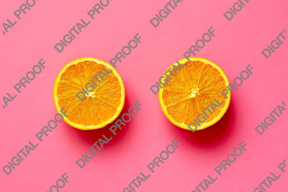 Orange fruit. Orange half fruit sliced isolate on fuscia background seen from above flatlay style, close up.